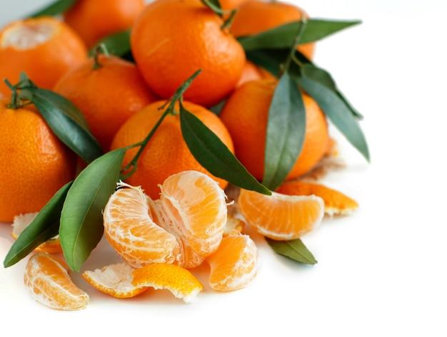 Mandarines avec feuilles isolées sur blanc gros plan