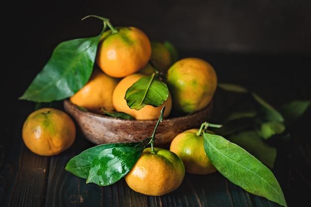 Mandarines avec des feuilles sur une table de pays à l'ancienne horizontale.
