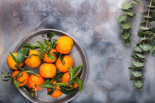 Mandarines à feuilles vertes sur une plaque métallique, sur fond gris