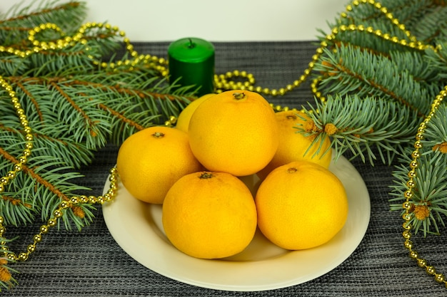 Mandarines sur fond de bougies et de branches de sapin. notion de noël et du nouvel an.