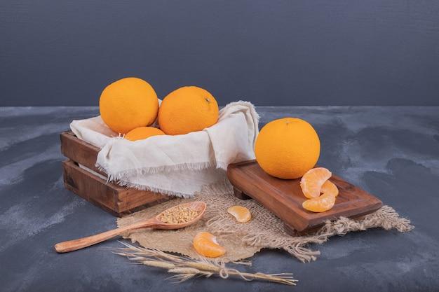 Mandarines fraîches dans une boîte en bois et tranches de mandarines sur toile de jute.