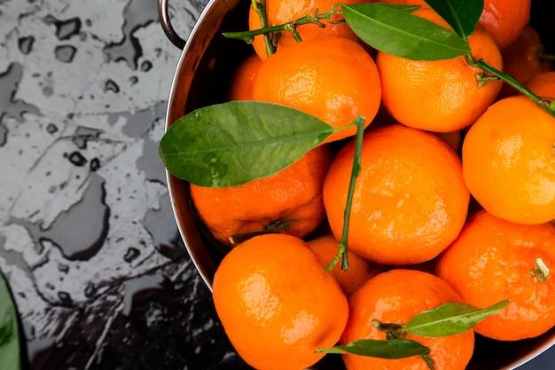 Mandarines fraîches dans le panier sur fond noir. fond d'agrumes. humide. macro