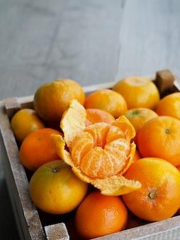 Mandarines fraîches dans une vieille boîte. sur fond en bois