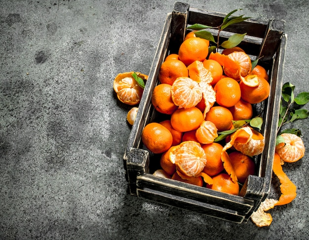 Mandarines fraîches dans une vieille boîte. sur un fond rustique.