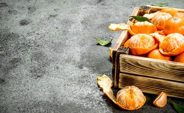 Mandarines fraîches dans une vieille boîte sur table rustique.