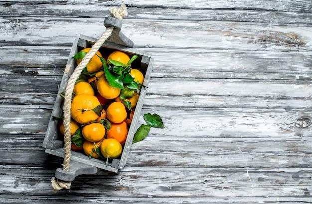 Mandarines fraîches avec des feuilles dans la boîte. sur fond de bois