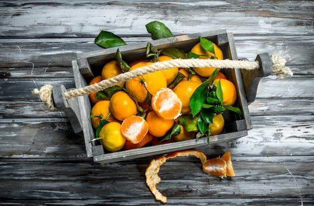 Mandarines fraîches avec des feuilles dans la boîte. sur table en bois