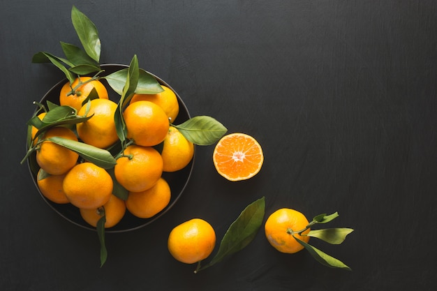 Mandarines fraîches avec des feuilles dans un bol sur fond noir. alimentation saine . espace de copie.