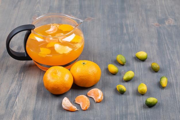 Mandarines fraîches et jus sur une surface en bois