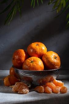 Mandarines fraîches juteuses dans une passoire en métal