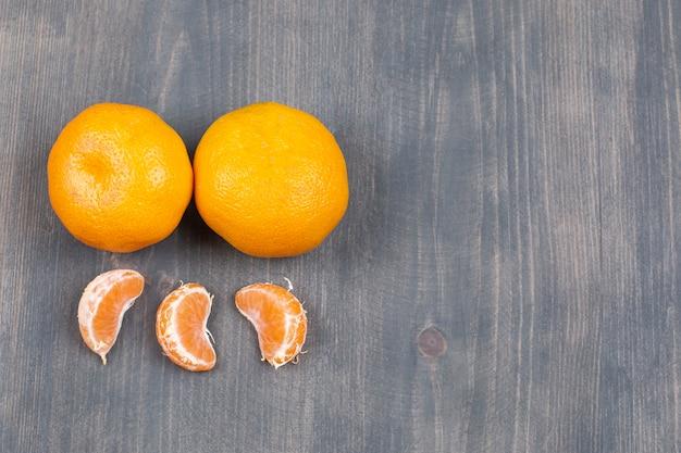Mandarines fraîches et segments sur table en bois