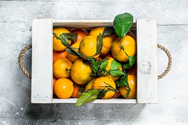 Mandarines juteuses jaunes avec des feuilles dans une boîte. sur table rustique