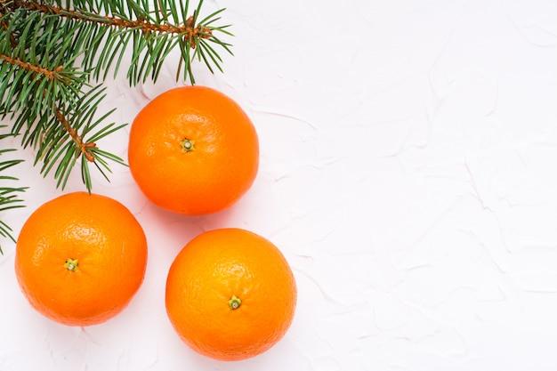 Mandarines mûres et branches de sapin sur une table blanche, vue de dessus