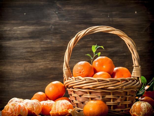 Mandarines mûres dans un panier sur un fond en bois