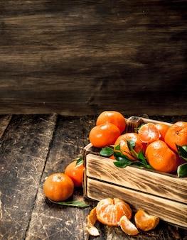 Mandarines mûres dans une vieille boîte sur table en bois.