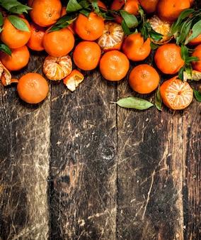 Mandarines mûres avec des feuilles sur un fond en bois