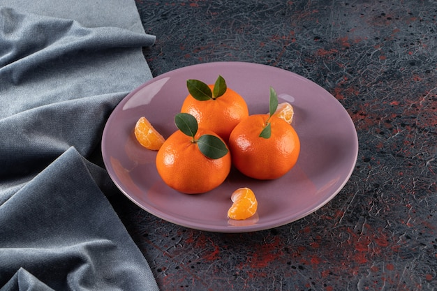 Mandarines mûres avec des feuilles placées sur une assiette violette.