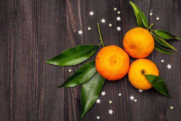 Mandarines mûres fraîches avec des feuilles et des paillettes.