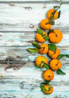 Mandarines mûres parfumées avec des feuilles. sur fond de bois