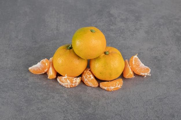 Mandarines mûres et segments sur fond de marbre. photo de haute qualité