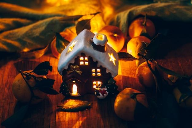 Mandarines de noël et une maison de jouets dans la nuit