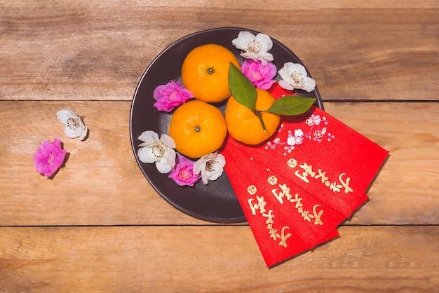 Mandarines et nouvel an lunaire avec texte « happy new year » sur la poche rouge. concept de vacances du têt. texte signifie chance et bonheur.