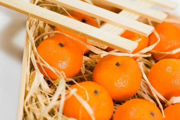 Mandarines avec paille dans une boîte en bois