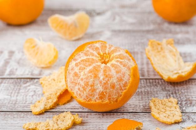 Mandarines pelées sur fond en bois
