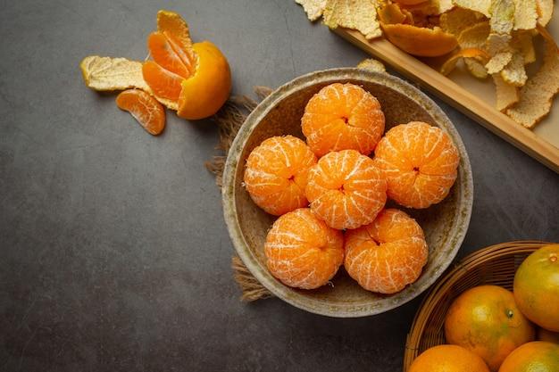 Mandarines pelées sur vieux fond sombre