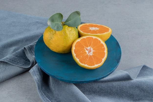 Mandarines sur une planche bleue sur un morceau de tissu, sur marbre