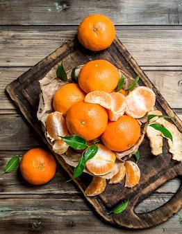 Mandarines sur la planche à découper. sur table en bois