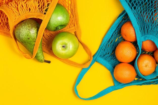 Mandarines et pommes vertes dans un sac de ficelle sur fond jaune.