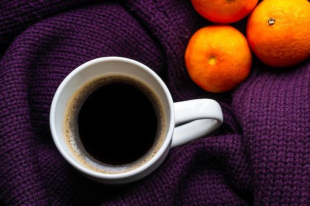 Mandarines et tasse de café sur un pull en tricot violet chaud