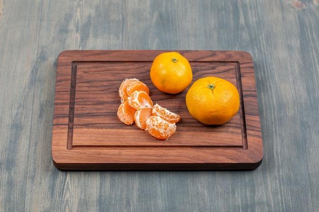 Mandarines tranchées et entières sur une planche à découper en bois