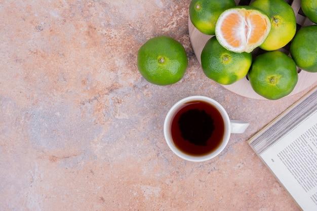 Mandarines vertes accompagnées d'une tasse de thé