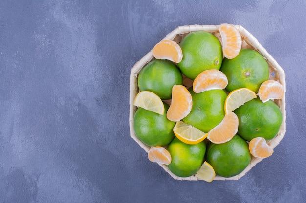 Mandarines vertes dans une assiette en bambou sur bleu.