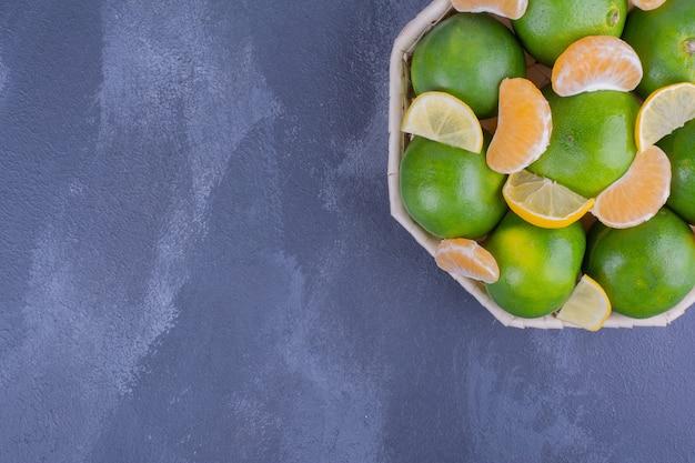 Mandarines vertes entières et pelées dans un panier en bambou.