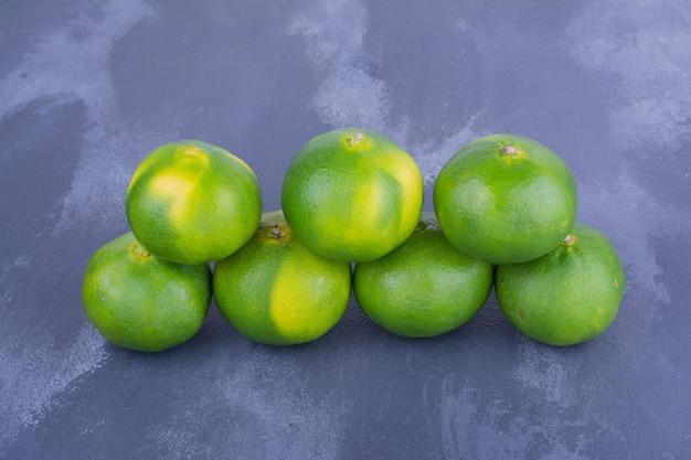 Mandarines vertes sur table bleue en rangée géométrique.