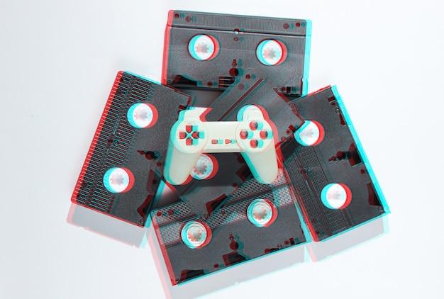 Manette de jeu sur cassettes vidéo rétro. studio de minimalisme tourné sur blanc.