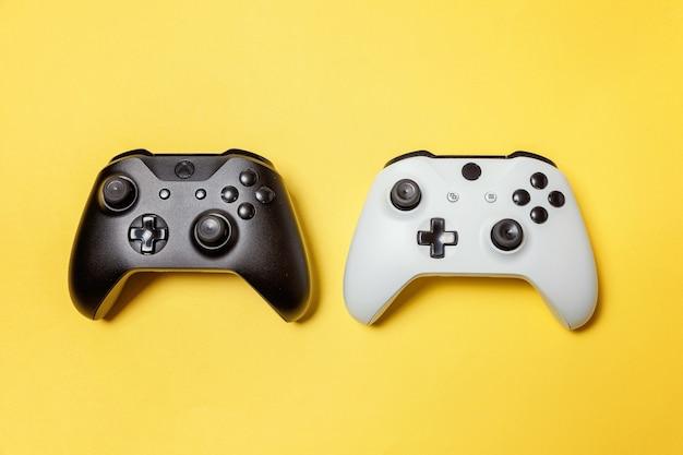 Manette de jeu deux joystick blanc et noir, console de jeu sur fond jaune