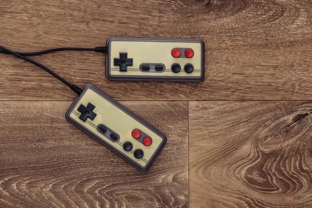 Manettes de jeu rétro sur un plancher en bois. vue de dessus