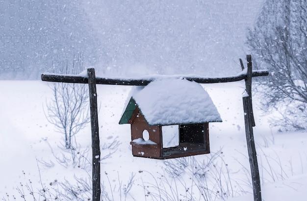 Mangeoire en bois suspendue à l'extérieur en hiver