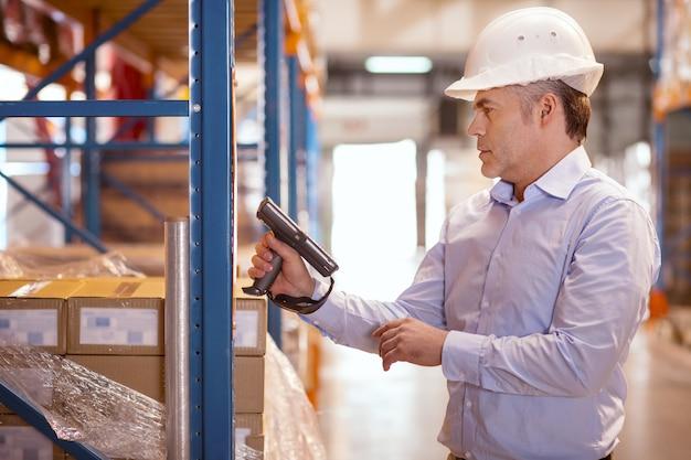 Mangeoire sérieuse et intelligente tenant un scanner tout en vérifiant l'équipement de l'entrepôt