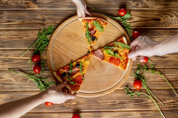 Manger des aliments. gros plan des mains de personnes prenant des tranches de pizza au pepperoni. groupe d'amis partageant une pizza ensemble.