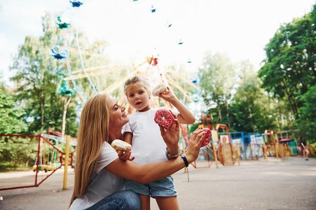 Manger des beignets. joyeuse petite fille sur patins à roulettes et sa mère s'amusent ensemble dans le parc près des attractions.