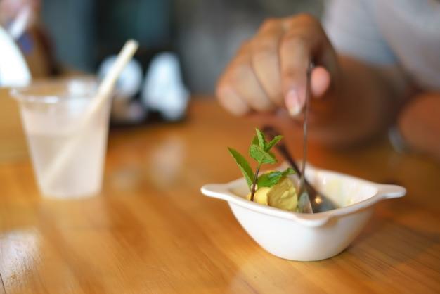 Manger une boule de glace à la mangue
