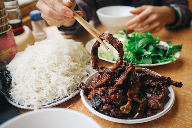 Manger un bun cha vietnamien avec des baguettes