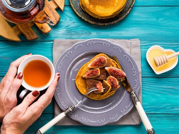 Manger des crêpes à la citrouille avec des figues et du miel