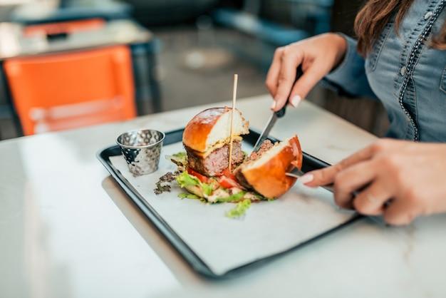 Manger un délicieux hamburger avec une fourchette et un couteau.