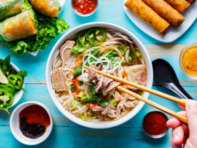 Manger du pho bo vietnamien coloré avec des baguettes de haut en bas